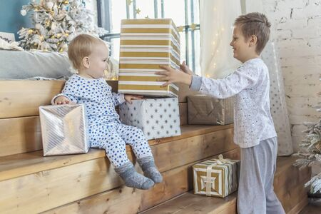 New Year's. A boy and a little girl in pajamas with gifts in boxes in a room with a Christmas tree.