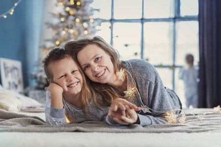 New Year's. Portrait of a smiling mother and little son lying on the bed against the background of a Christmas tree and a window