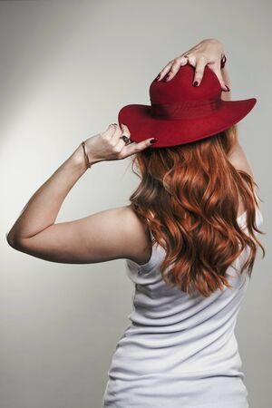 Red-haired girl in a red hat, view from the back. Studio photo Banque d'images - 145109054