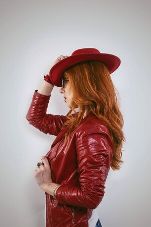Young red-haired woman in a red jacket and hat. Side view. Studio photo Banque d'images - 140017383