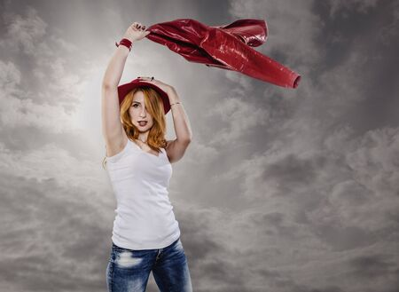 Red-haired young woman in a red hat waving a leather jacket over her head against a cloudy gray sky. Banque d'images - 145109062