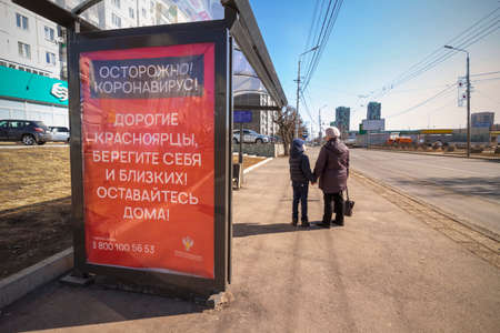 Krasnoyarsk, Russia - April 6, 2020: A woman with a child at a bus stop and a poster urging them to stay home during the coronavirus epidemic Banque d'images - 145095982