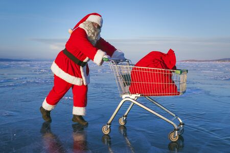 Santa Claus with a shopping trolley in which lies a bag with gifts on a frozen winter lake Banque d'images - 147238220