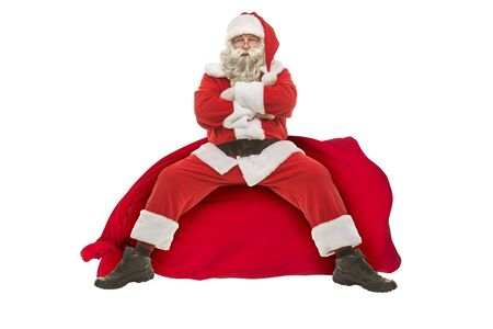 Santa Claus sits on a bag with gifts on a white background, photo collage