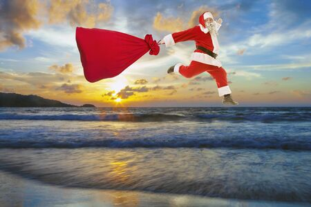 Santa Claus with a big bag of gifts lands on the beach Banque d'images - 146722745