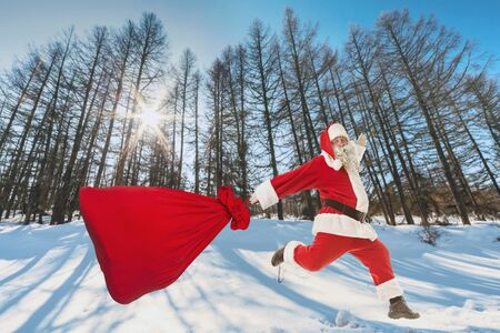 Santa Claus with a big bag of gifts lands in the winter forest