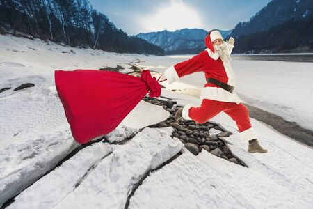 Santa Claus with a big bag of gifts lands on the frozen ice of the river Banco de Imagens