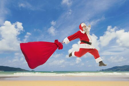 Santa Claus with a big bag of gifts lands on the beach Banque d'images - 146724648