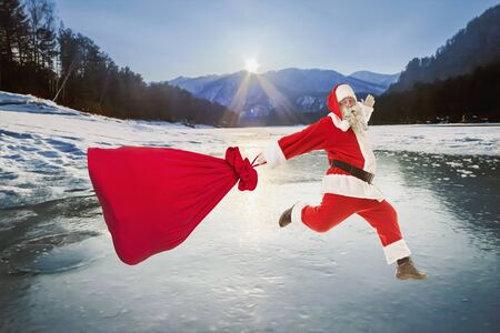 Santa Claus with a big bag of gifts lands on the frozen ice of the lake Banco de Imagens
