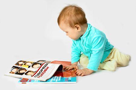 baby read the magazine on white photo