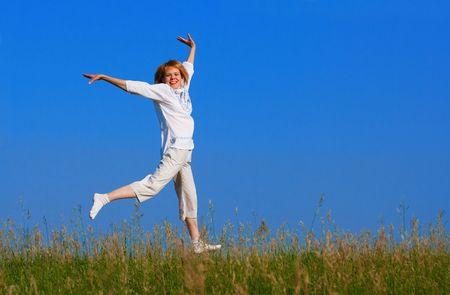 cian: beauty girl jumping in field under blue sky