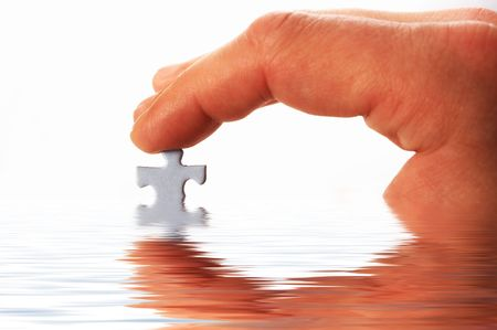 finger and puzzle in water on white photo