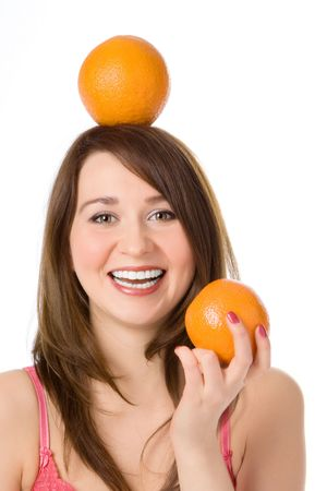 smiling pretty girl with orange on head fnd hand on white background photo