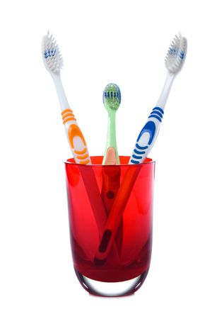 remedial: family tree toothbrush in red glass on white background
