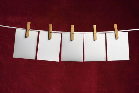 adjuntar: cinco en blanco de la hoja de papel conceden a la cuerda de ropa clavija en rojo  Foto de archivo