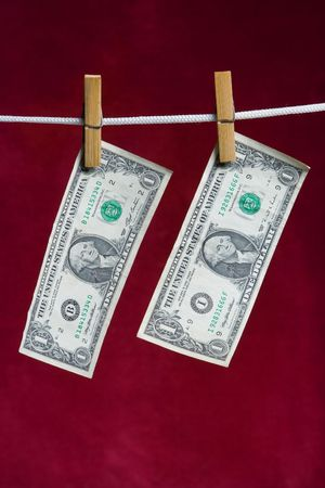attach: two american dollar attach to rope clothes peg on red Stock Photo