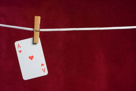 fervour: heart ace with clothes peg  rope on red background Stock Photo