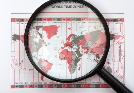 time zones: black magnifier on world map with time zones