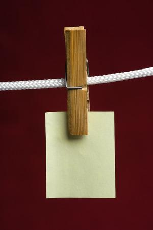 załączyć: żółty papier dołączyć ubrania-PEG do liny na tle winnego