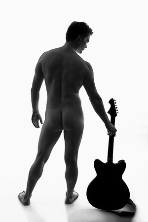 naked man: young naked man with guitar