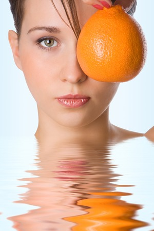 bodyscape: yung beauty girl hold orange  front of eye