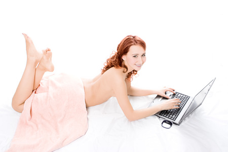 spa naked red beautiful girl lays on white covered by a pink towel and works on laptop photo