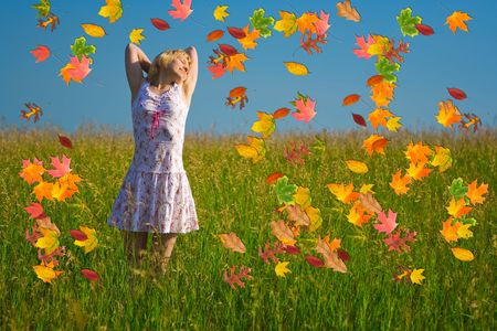 Beauty happy woman in fieldand autumn leaf photo