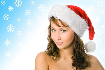 curly-headed beauty woman in red santa cap on blue background with snowflake photo