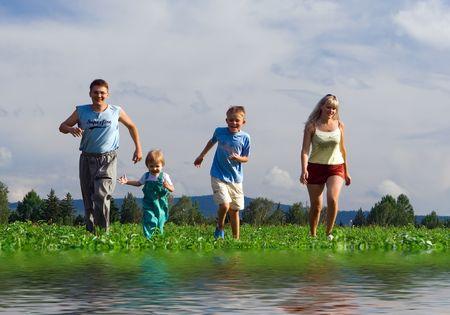family with two children running on field with water reflection in front photo