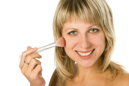 close-up portrait of woman applying blusher on her cheek over white background photo