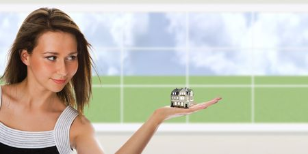 executive apartment: Young beautiful  woman hold a little house on hand in interior