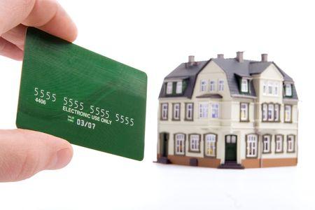mano e pagamento con carta di plastica per la casa su sfondo bianco  Archivio Fotografico