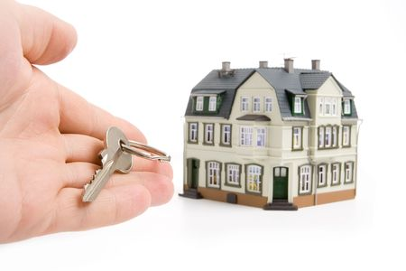 occupancy: hand with key for house over white background