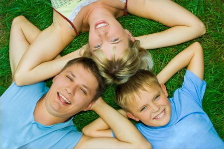 happy family three people on green grass photo