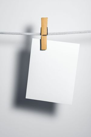 attach: white paper blank on rope attach clothes-peg Stock Photo