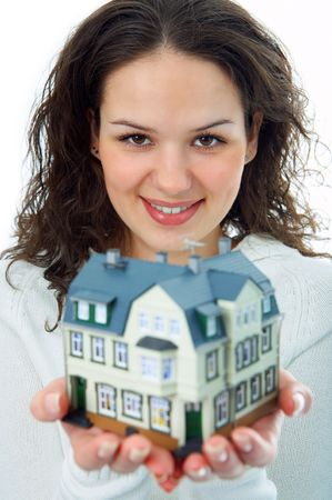young woman with little house in hand on white photo
