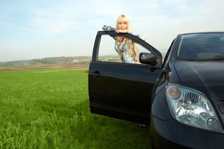 woman with car in field photo