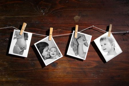 Pictures of a newborn and mother attach to rope with clothes spins on wooden background Stock Photo