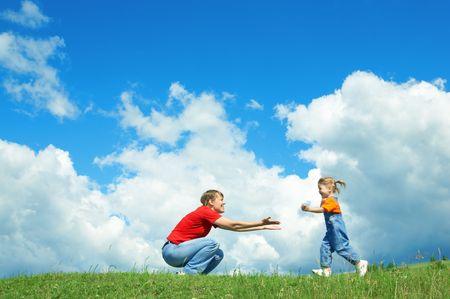 petite fille � la m�re courir embrasser sur l'herbe verte sous le ciel avec les nuages