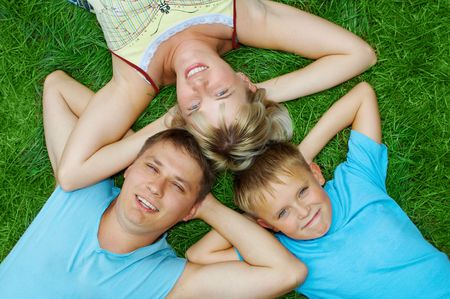 happy family lie on green grass photo