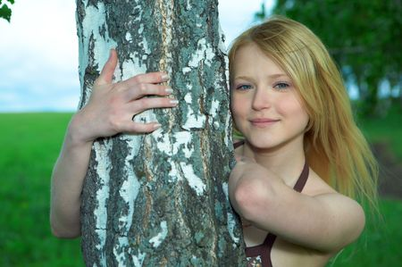 herbage: young woman in field with birch tree Stock Photo