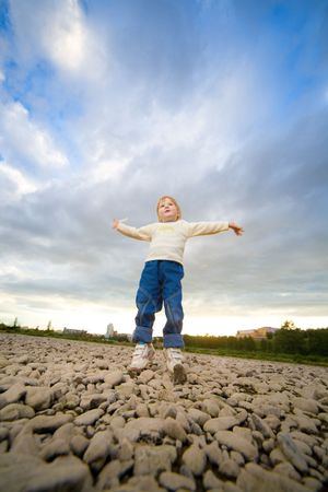 foreshortening: little girl jump under blue sky with clouds Stock Photo