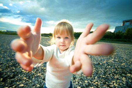 foreshortening: little girl grief look and reach out hands Stock Photo