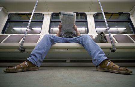 foreshortening: businessman reading newspaper in metro carriage