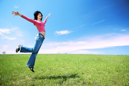 happy woman jump in field under blue sky and clouds photo