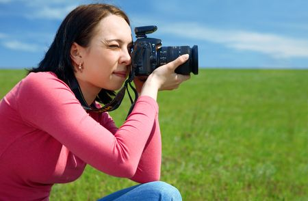 woman photographer in field under blue sky and clouds photo