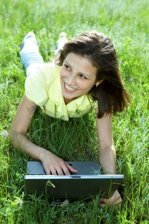 pretty woman with laptop on the green grass under blue sky Stock Photo - 3846522