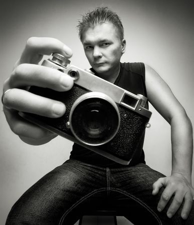 foreshortening: photographer with camera portrait shoot wide angle lens on gray background