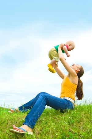 Mother with  baby  on the meadow under blue sky Stock Photo