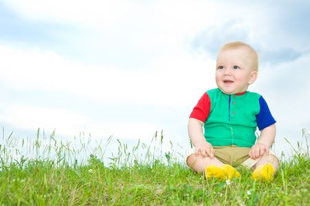 liitle baby sit on grass under blue sky photo